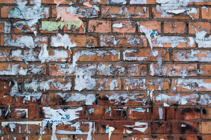 Brick Wall with Torn Ads. Brown Brickwall Glued Randomly And Scraped Stickers. royalty free stock image