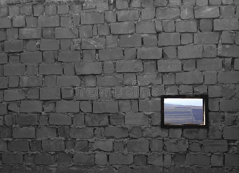 Unfinished brick wall with a window, with a rustic landscape. Image of a grey brick wall with a window, with a great texture and a rustic landscape royalty free stock photo