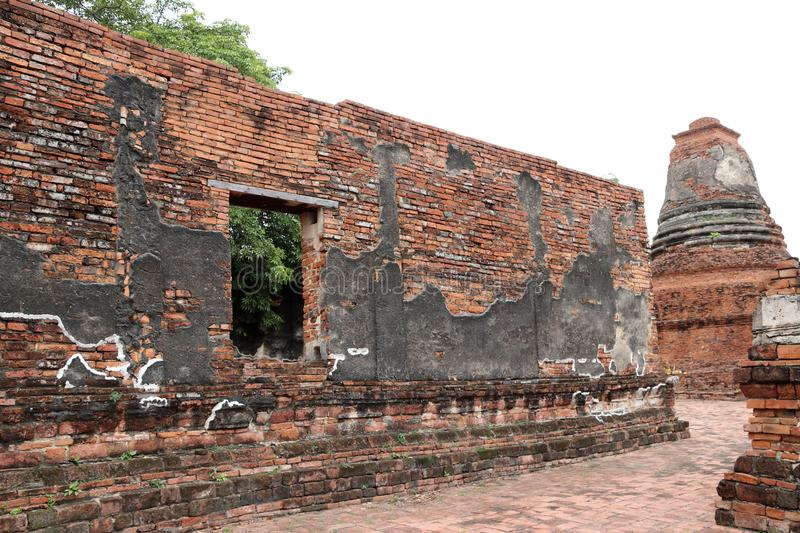 The brick wall with window of church and small stupa in the ruins of ancient remains at Wat Worachet temple. royalty free stock photography