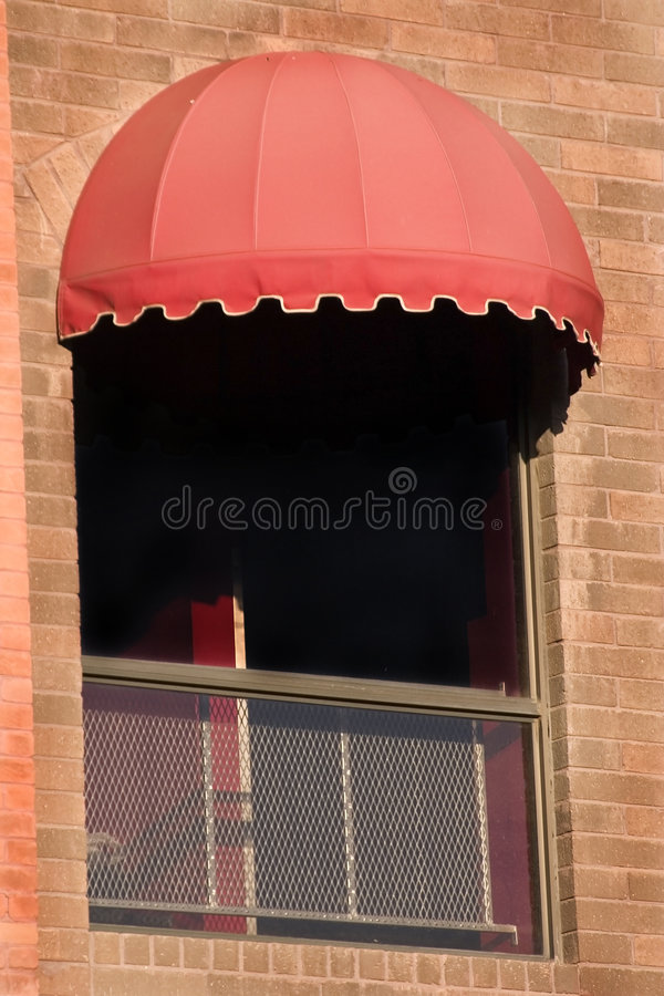 Brick Wall and A Window with Red Awning royalty free stock photo