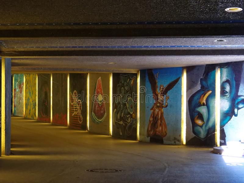 Pedestrian underpass with decorative graffiti art. The brick walls in a pedestrian underpass decoratively painted with graffiti. Elaborate wall paintings in a stock image