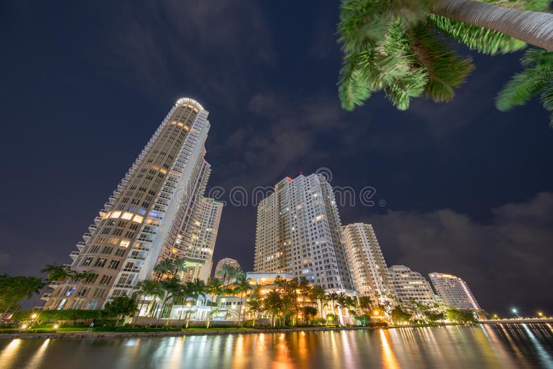 Brickell Key Miami highrise condominiums. Long exposure photo shot at night with blurry clouds and palm trees. Water smooth. Surface USA royalty free stock image