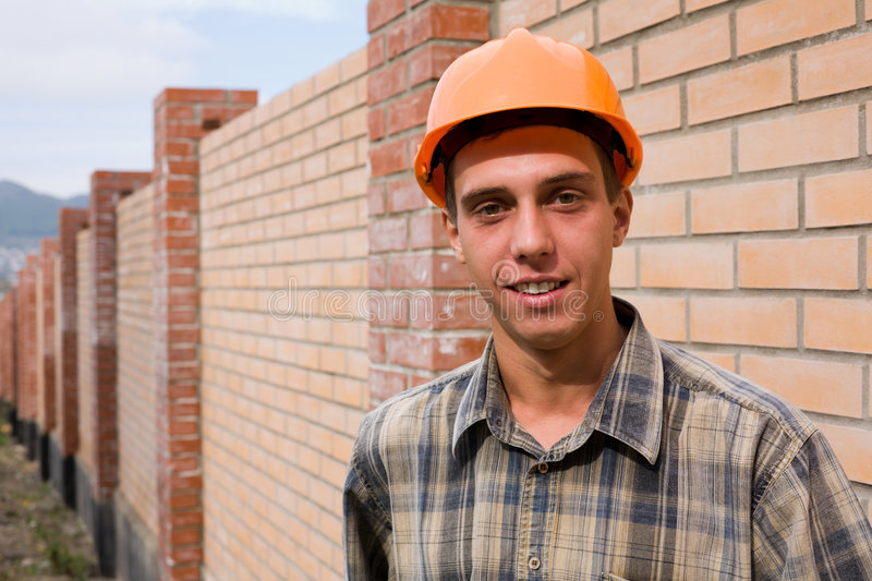 Bricklayer. The young mason on a background of a new brick wall royalty free stock image
