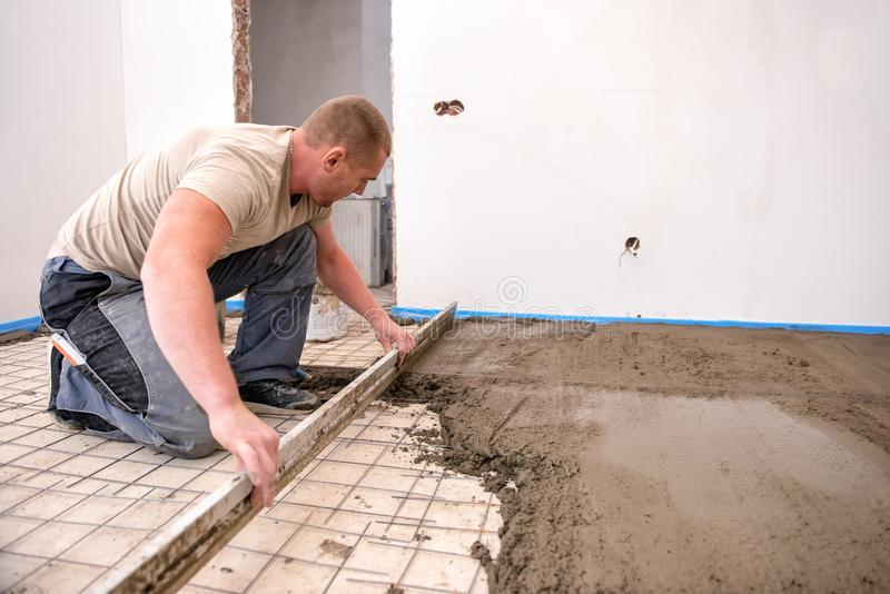 Bricklayer aligns cement screed in a newly built house royalty free stock photography