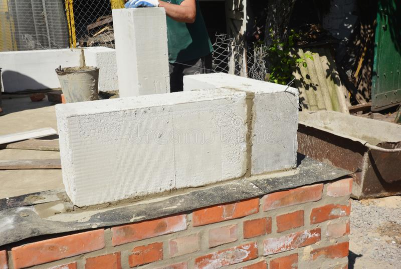 Bricklayer builder laying autoclaved aerated concrete blocks, aac on house foundation wall. Outdoor stock photo