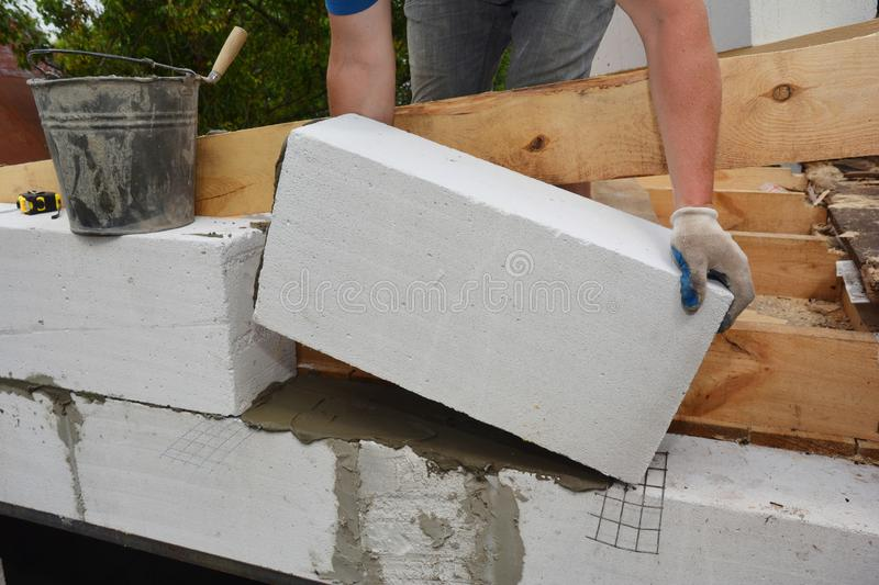 Bricklayer builder laying autoclaved aerated concrete blocks, aac for house wall. Photo stock photography
