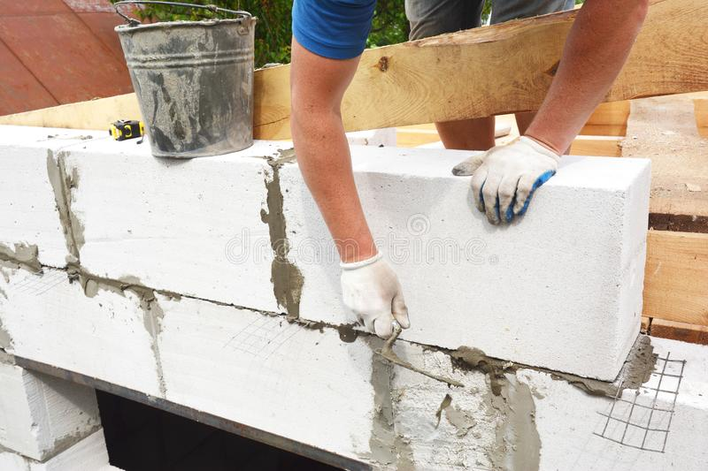 Bricklayer builder laying autoclaved aerated concrete blocks for house wall near unfinished roof wooden beams stock images