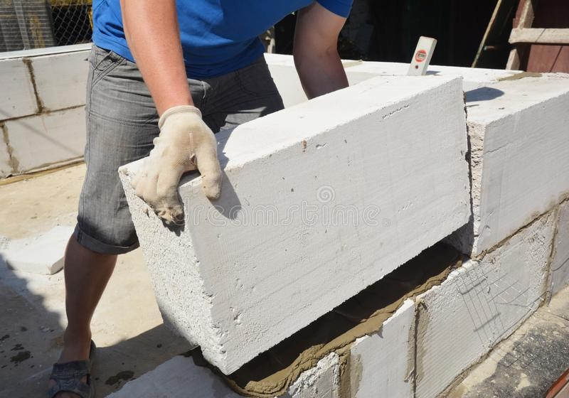 Bricklayer builder laying autoclaved aerated concrete blocks for house wall. Photo royalty free stock photography