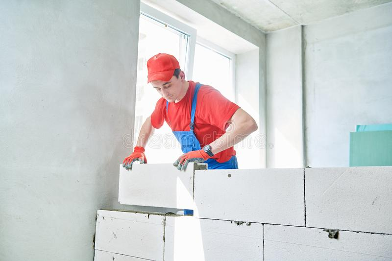 Bricklayer builder working with autoclaved aerated concrete blocks. Walling. Bricklaying construction work or walling. bricklayer builder working with autoclaved stock images