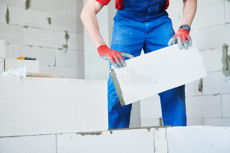 Bricklayer builder working with autoclaved aerated concrete blocks. Walling. Bricklaying construction work or walling. bricklayer builder working with autoclaved stock photos