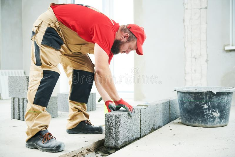 Bricklayer builder working with ceramsite concrete blocks. Walling. Bricklaying construction work or walling. bricklayer builder working with ceramsite concrete stock photo