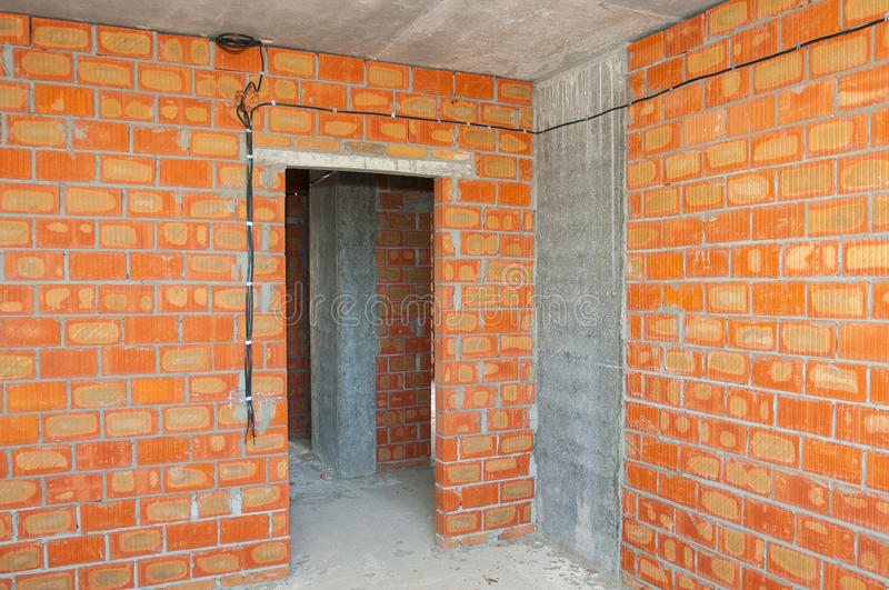Bricklayer building new house with brick walls, interior rooms,wiring.  stock photo