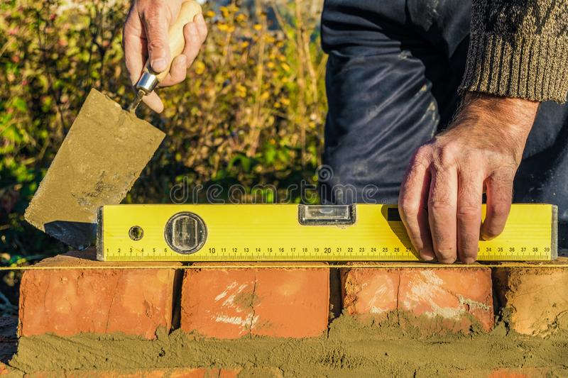 Bricklayer checks the horizontal level of brick masonry wall with a bubble level. Construction worker stock image