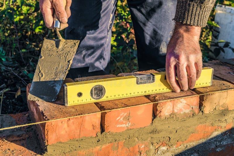 Bricklayer checks the horizontal level of brick masonry wall with a bubble level. Construction worker royalty free stock photo
