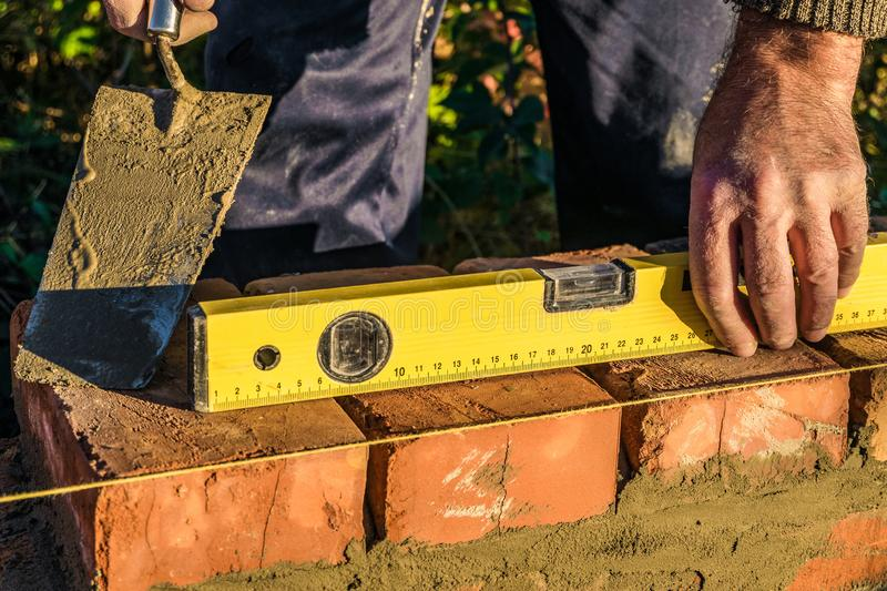Bricklayer checks the horizontal level of brick masonry wall with a bubble level and and lacing cord. Bubble centered. Outdoors building stock photography