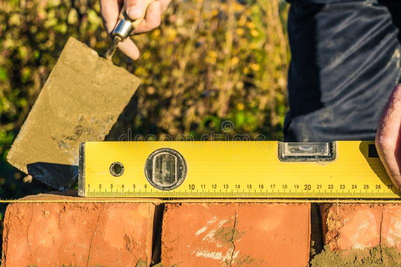 Bricklayer checks the horizontal level of brick masonry wall with a bubble level and and lacing cord. Bubble centered royalty free stock images
