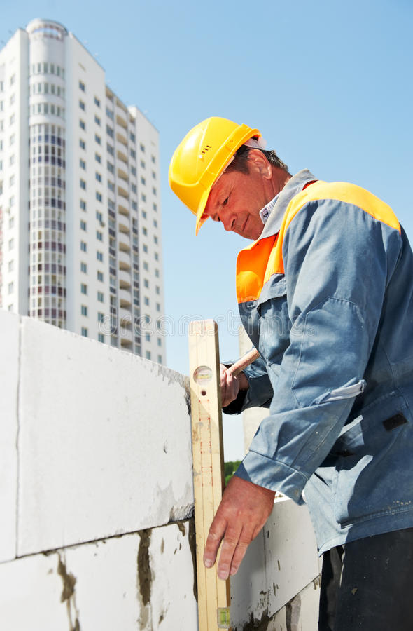 Bricklayer at construction masonry. Construction mason worker checking quality of bricklaying with measuring level royalty free stock images