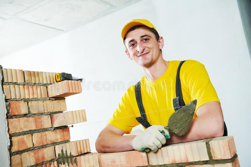 Bricklayer. Portrait of young smiling construction mason near brick wall stock image