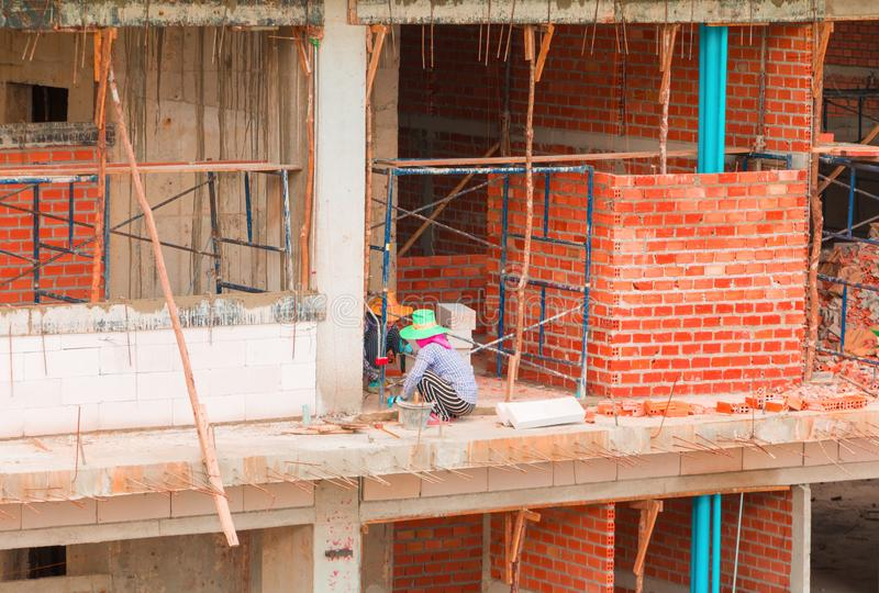 Bricklayer Female worker work industrial installing wall bricks in construction site stock photo