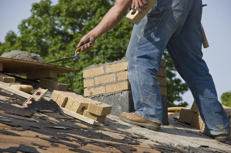 Bricklayer Mason Laying Chimney Bricks on House