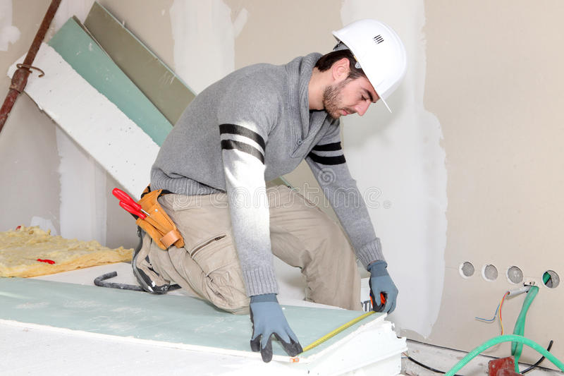 Bricklayer measuring plasterboard. Worker in a room under construction royalty free stock photography