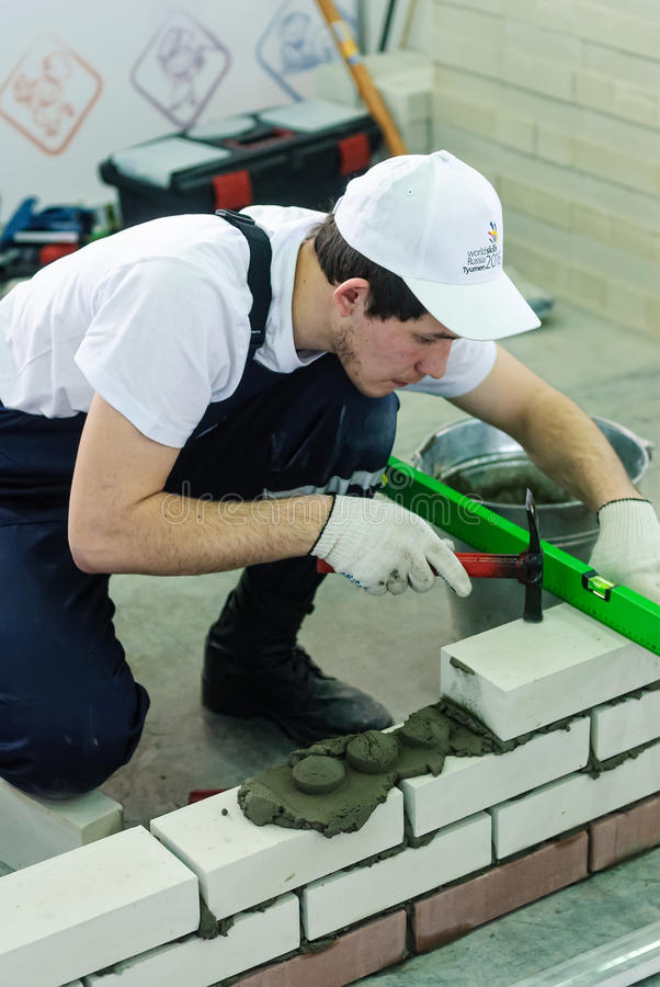 Bricklayer performs a task of competition. Tyumen, Russia - March 23. 2016: Open championship of professional skill among youth. World skills Russia Tyumen stock images