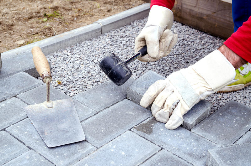Bricklayer places concrete paving stone blocks for building up a. Patio, using hammer royalty free stock image