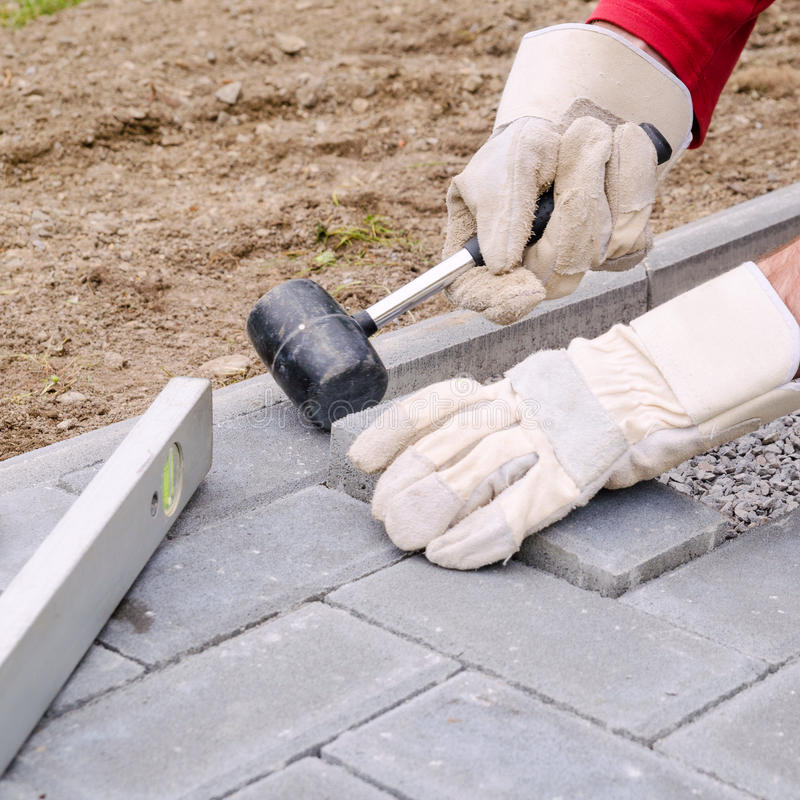 Bricklayer places concrete paving stone blocks for building up a pave patio, using hammer and spirit level. Handyman DIY concept.  royalty free stock photos