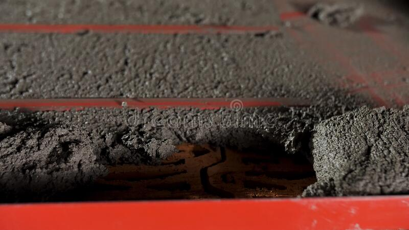 Bricklayer putting down another row of cement using a special red form. Stock footage. Close up of building wall process stock photography