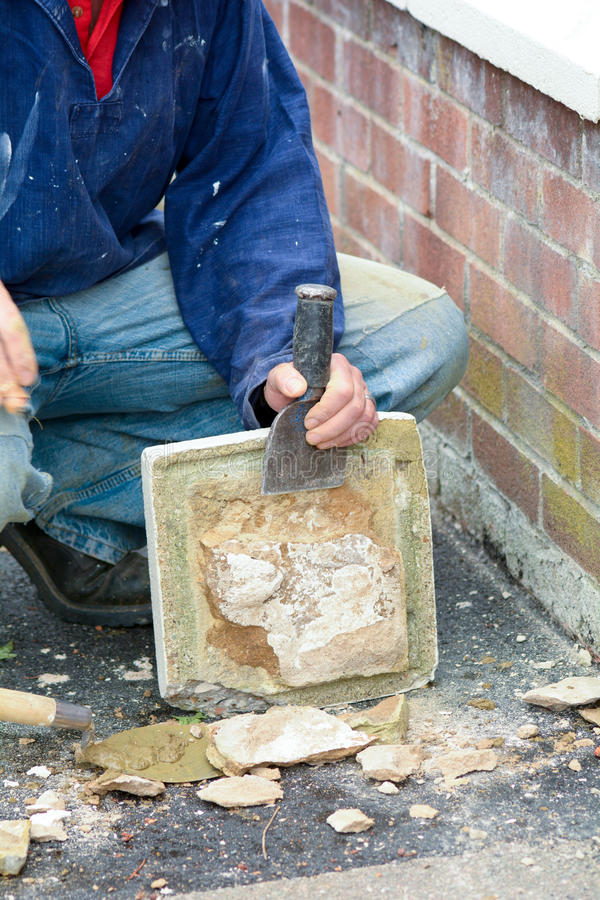 Bricklayer using lump hammer and bolster. To clear old render off gate topper stock photography