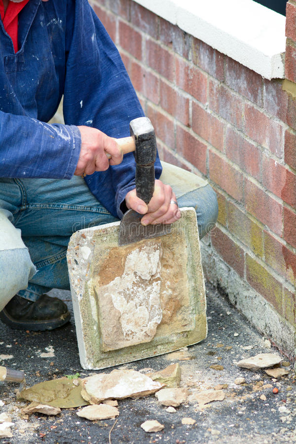 Bricklayer using lump hammer and bolster. To clear old render off post topper stock photo