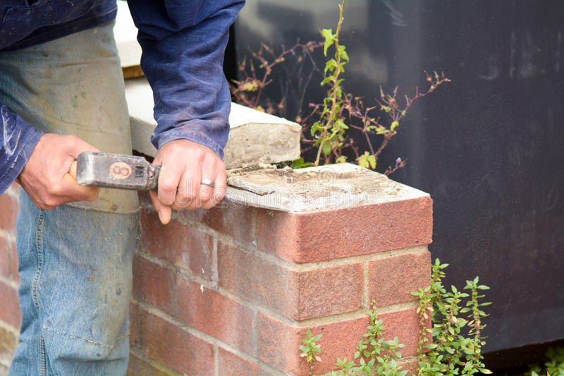Bricklayer using lump hammer and bolster to clear old render. Off wall stock photos