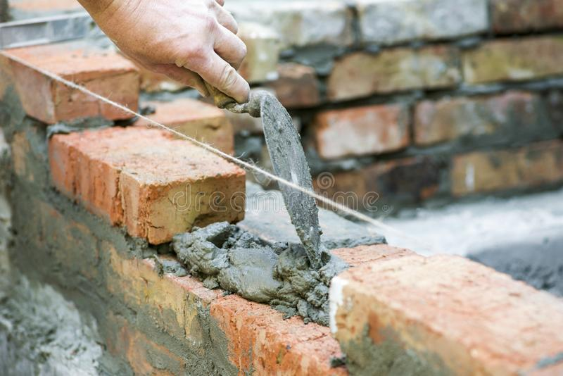 Bricklayer worker installing brick masonry on exterior wall. Professional construction worker laying bricks. Bricklayer worker stock photo