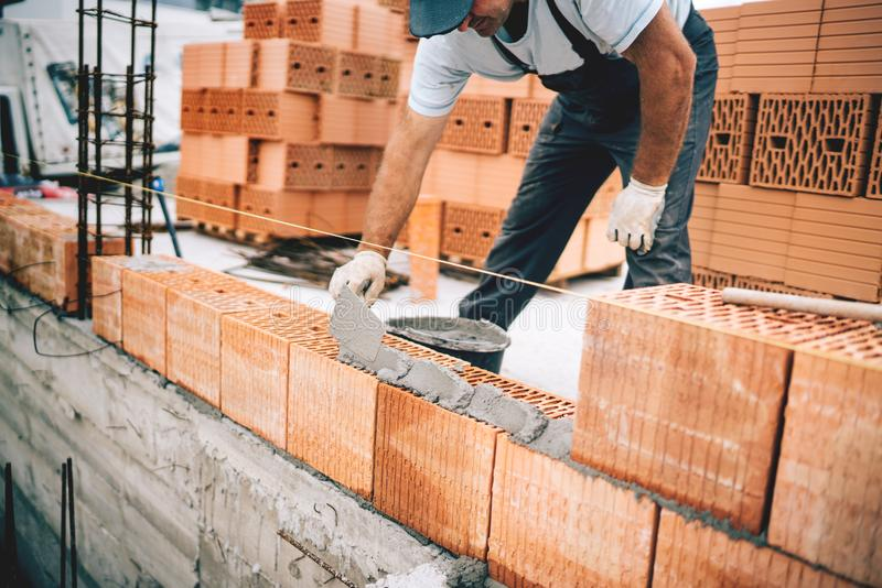 Bricklayer worker installing brick masonry on exterior wall with trowel putty knife. Bricklayer industrial worker installing brick masonry on exterior wall with stock photos