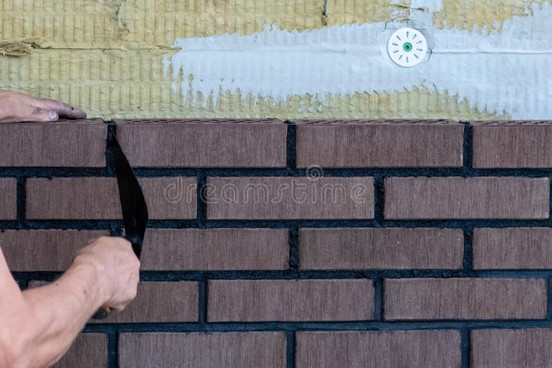 Bricklayer worker installing bricks on construction site. royalty free stock images
