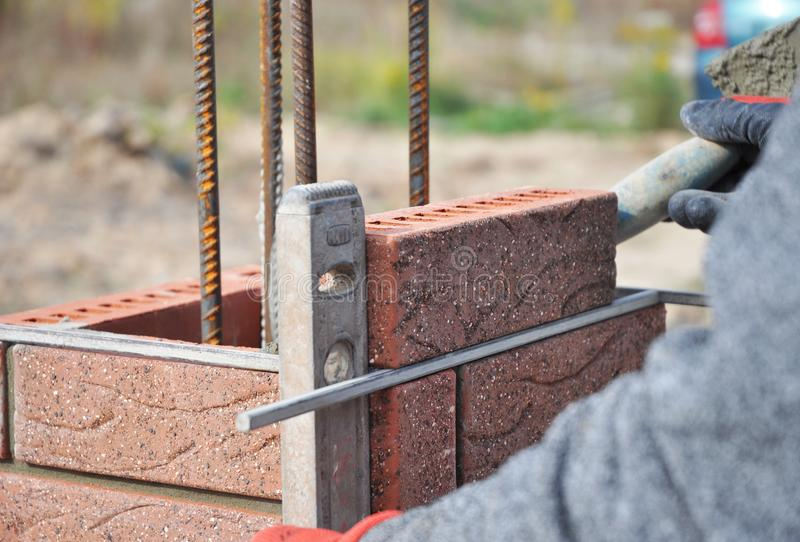 Bricklayer Worker Installing Red Clinker Blocks and Caulking Brick Masonry Joints Exterior Wall with Trowel putty Knife. And Fixing with Spirit Level stock images