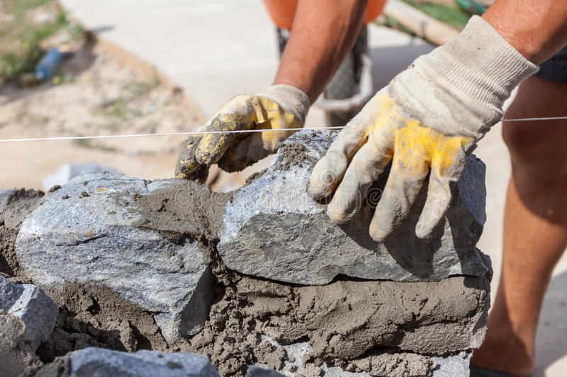 Bricklayer worker in protection yellow gloves installing stones. royalty free stock photography