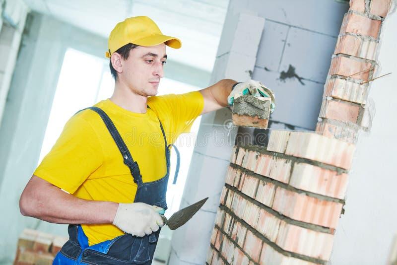 bricklaying Bouwvakker die bakstenen muur leggen stock afbeelding