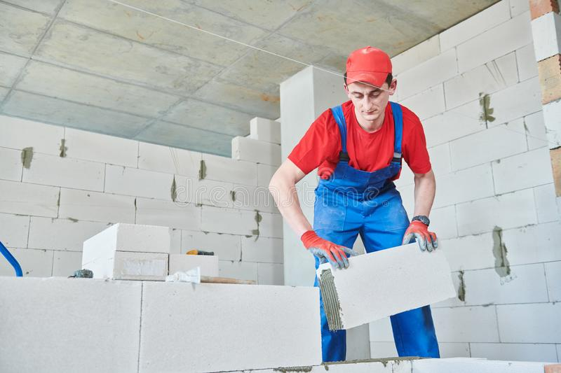 Bricklayer builder working with autoclaved aerated concrete blocks. Walling. Bricklaying construction work or walling. bricklayer builder working with autoclaved stock photo
