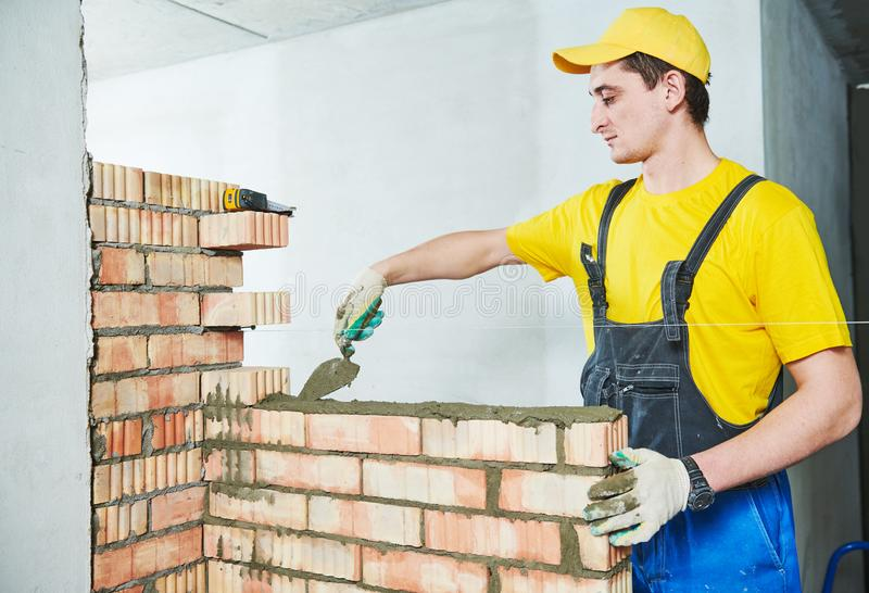 Bricklaying. Construction worker building a brick wall royalty free stock image