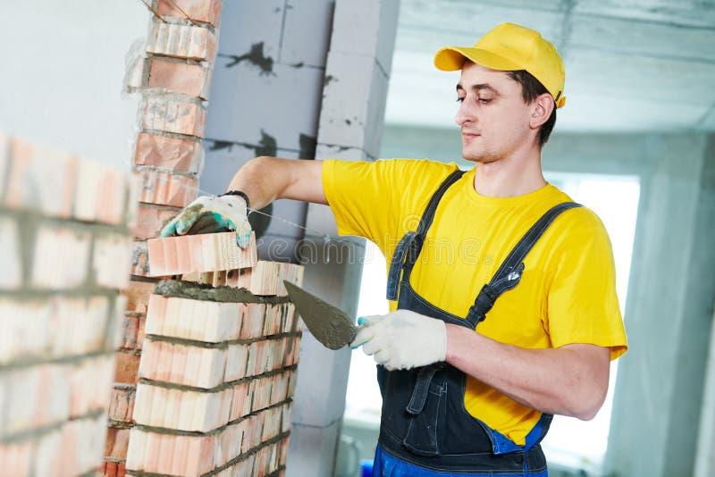 bricklaying De bouwvakkerbouw een bakstenen muur stock afbeelding