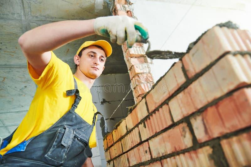 bricklaying De bouwvakkerbouw een bakstenen muur stock foto's