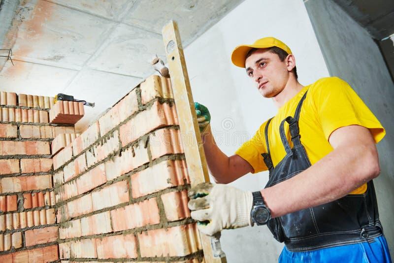bricklaying I controlli del lavoratore hanno eretto il muro di mattoni con il livello fotografie stock libere da diritti