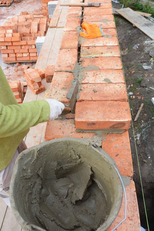 bricklaying Metselaarsarbeider die rode bakstenen muur met het mes installeren van de troffelstopverf openlucht Metselaarsarbeide stock foto's