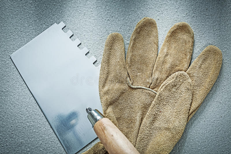Bricklaying trowel working gloves on concrete background constru. Ction concept royalty free stock images