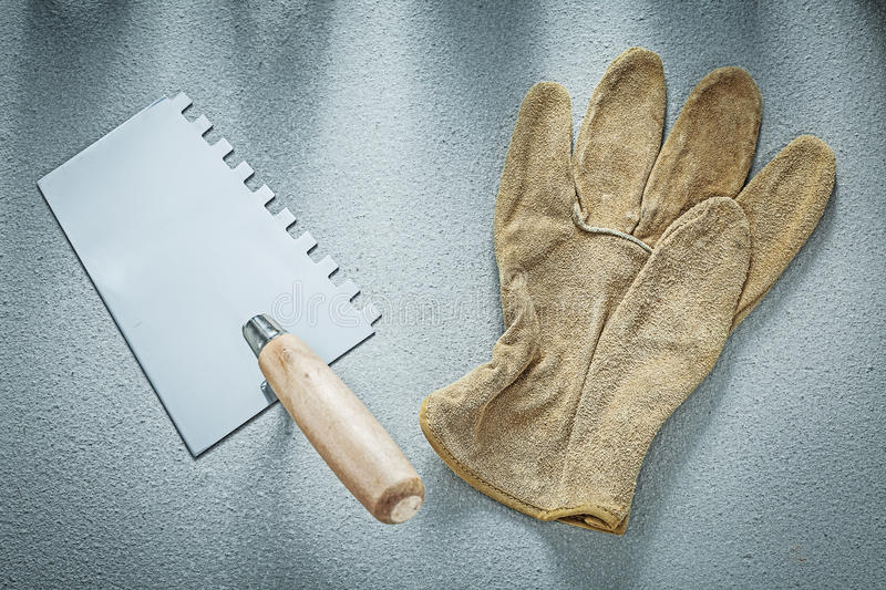 Bricklaying trowel working gloves on concrete surface constructi. On concept stock photos