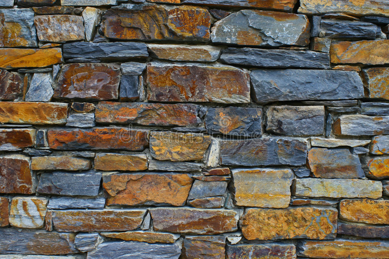 Bricks. Orange and gray bricks stacked to make the foundation of a building royalty free stock photos