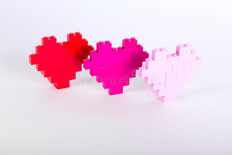 The bricks of the plastic constructor in the form of hearts are red, magenta, pink. White background. stock photos