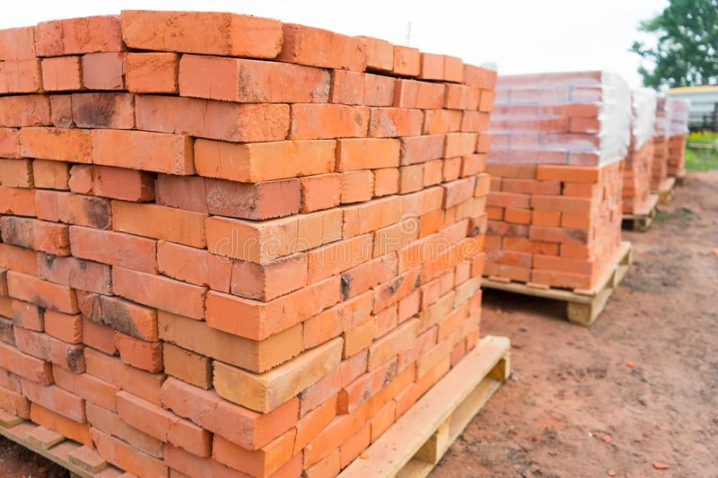 The bricks are stacked on wooden pallets and prepared for sale. Clay brick is an ecological building material.  stock photography