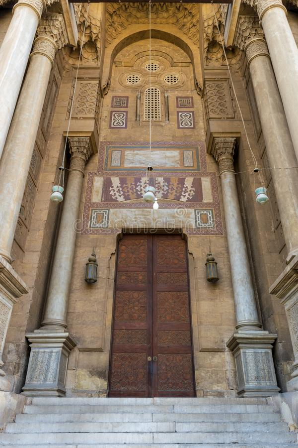 Bricks stone wall with arabesque decorated wooden door and marble engraved columns, al Refai Mosque. Side entrance of al Rifai Mosque, old decorated bricks stone stock image